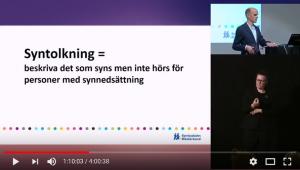 Skärmbild från videospelare som visar föreläsare, teckenspråkstolk och en presentationsbild med följande text: Syntolkning = beskriva det som syns men inte hörs för personer med synnedsättning.